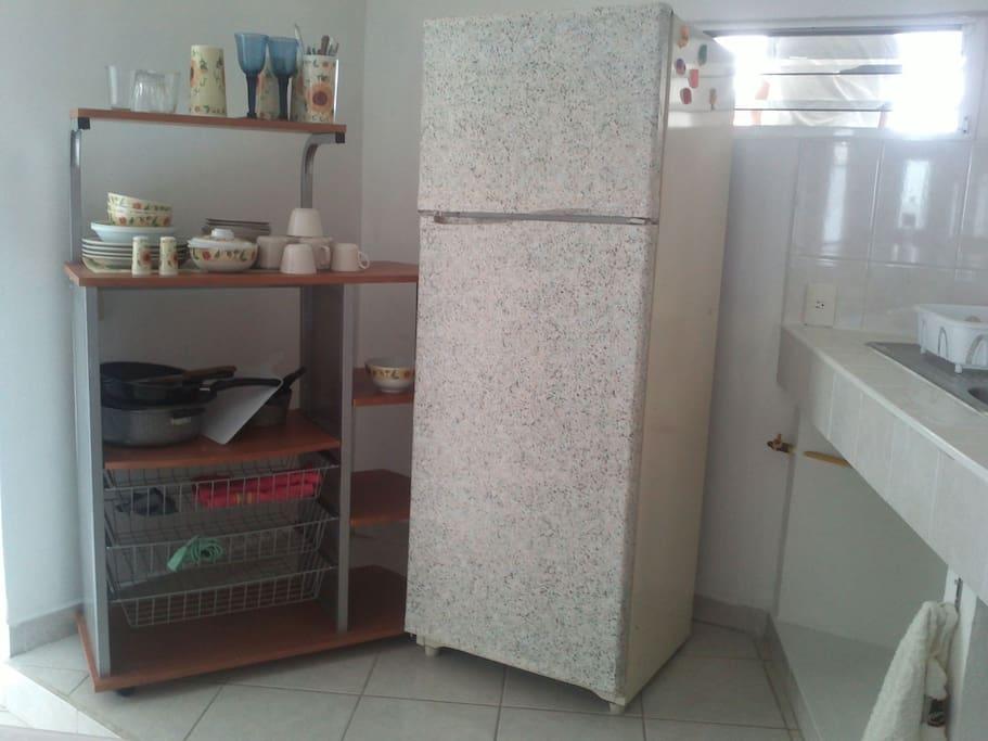 Cocina con vajilla, cubiertos, estufa y refrigerador
