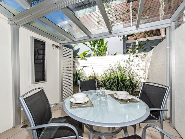 Private Rear Courtyard with covered outdoor furniture area. Bifold doors allow full access.