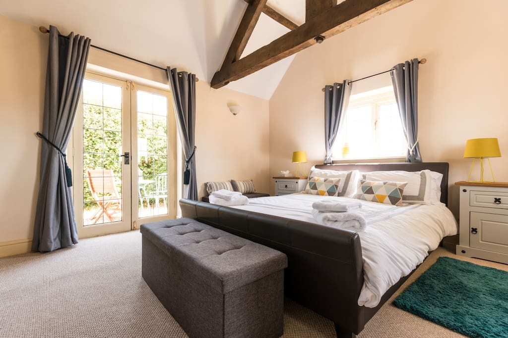 Large bedroom with king sized bed and french doors overlooking the gravel seating area