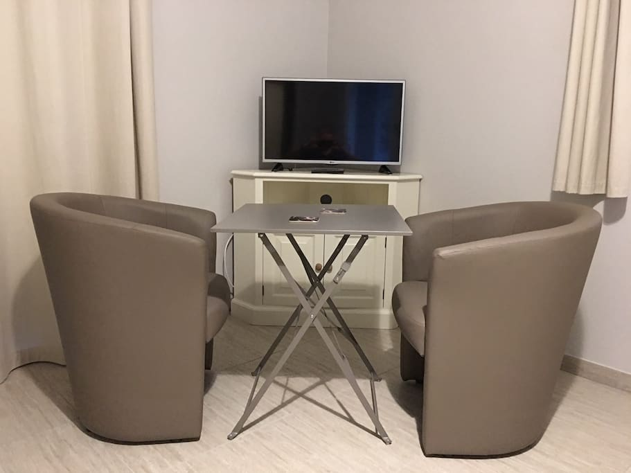Table, chairs, and flat screen TV.