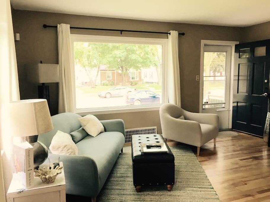 comfy living area with big window on a tree lined street