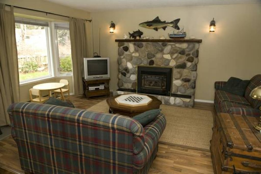 Comfortable family room with river rock gas fireplace. New couches since this picture was taken, a tv with DVD player and a beautiful view out the window!