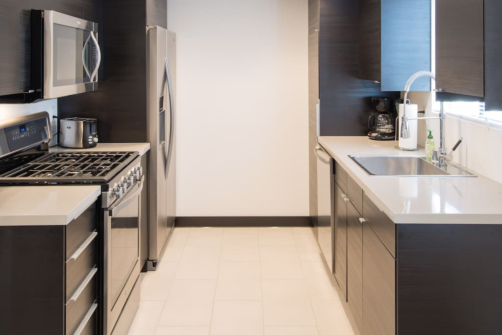 Brand new kitchen with quartz countertops, stainless appliances, fridge with ice maker, and filtered water dispenser