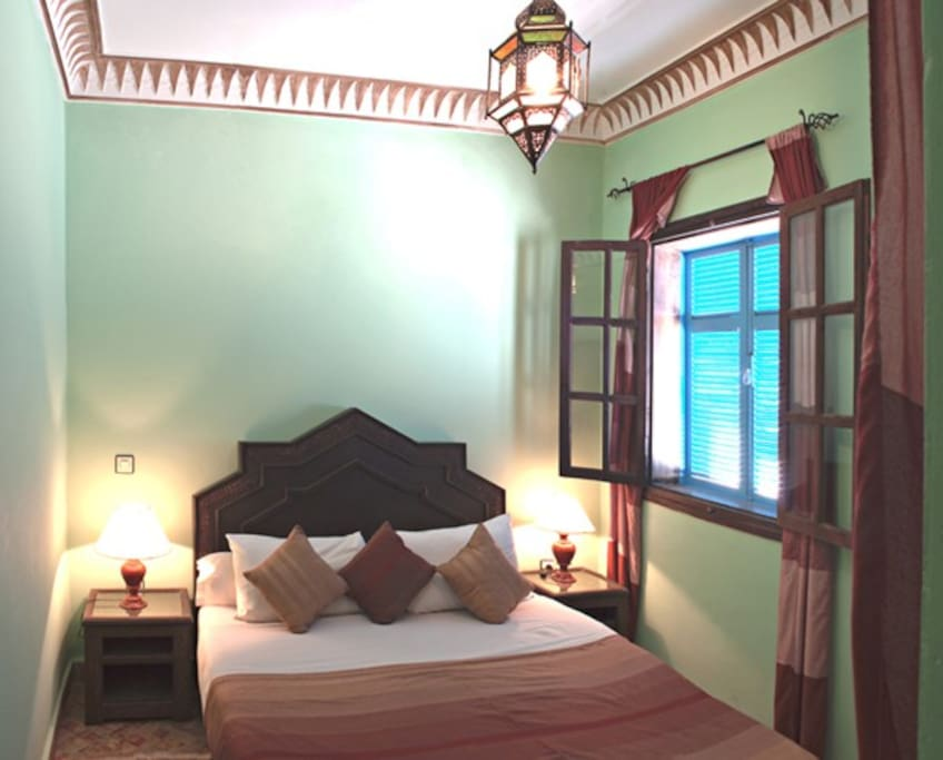 chambre a coucher avec un grand lit , avec une vue sur la rue