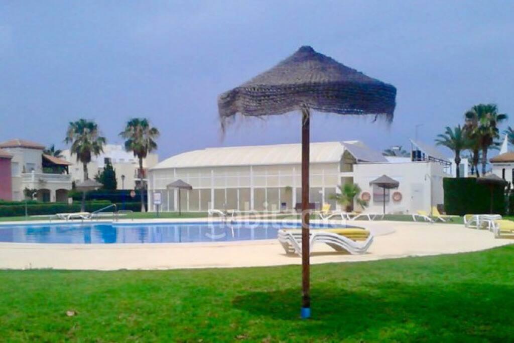 Piscina abierta con la piscina cubierta al fondo