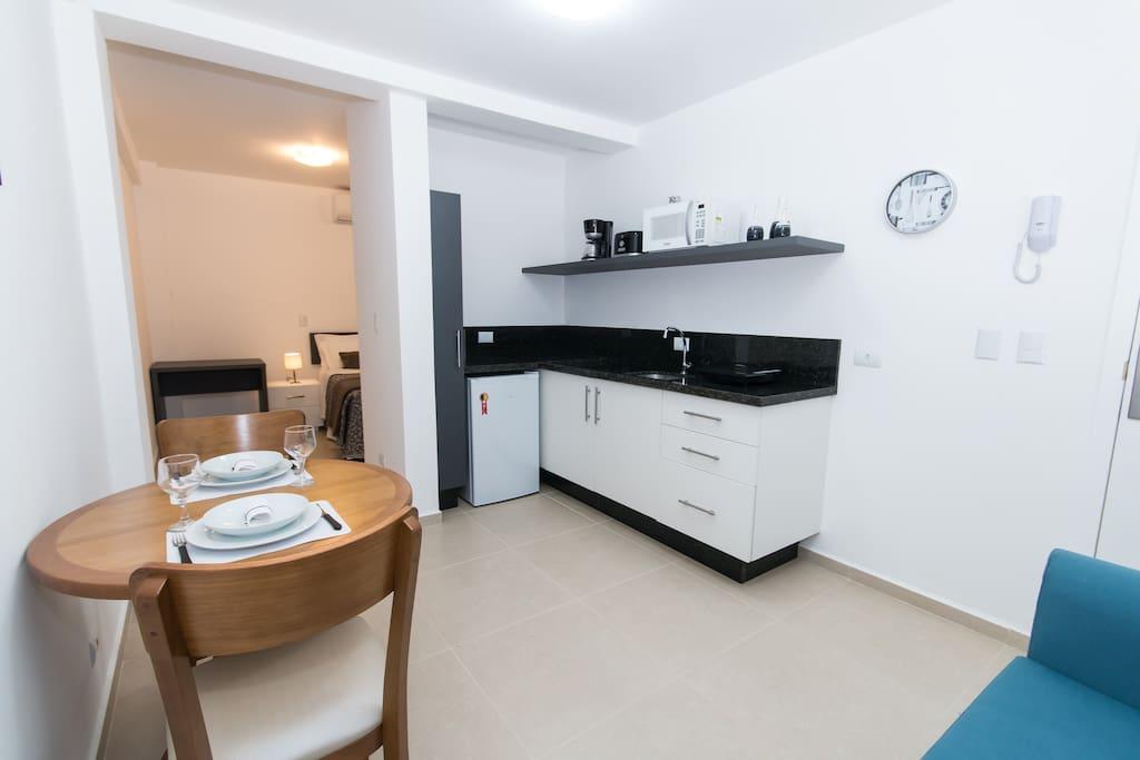Cozinha completa com fogão, microondas, cafeteira, torradeira, louças e utensílios