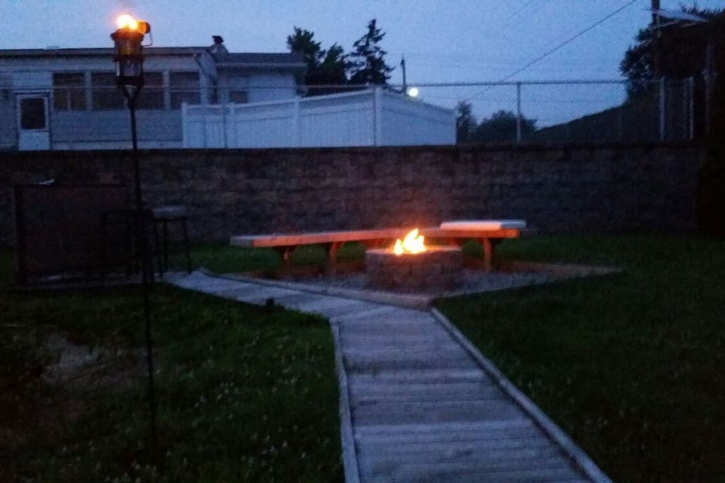 Garden side fire pit with seating for 10, plush chairs, 2 benches, plus additional seating on the patio