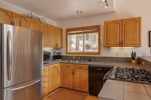 Open kitchen with dishwasher, new gas stove and refrigerator