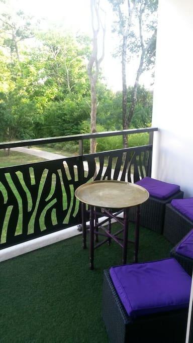 Grand balcon avec un coin cocooning donnant sur un parc arboré