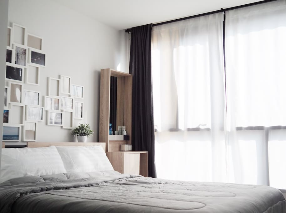 Bedroom with morning light, comfortable queen size bed and dressing table.