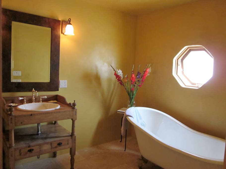 Upstairs Bathroom with 'single-slipper' bear claw tub, 1890's wood sink cabinet, 7-shower-head shower, copper framed-beveled mirror and travertine stone heated floor.
