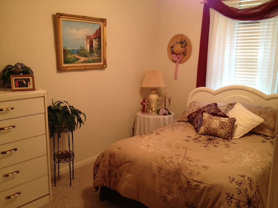 Comfortable double bed with closet and 2 dressers.