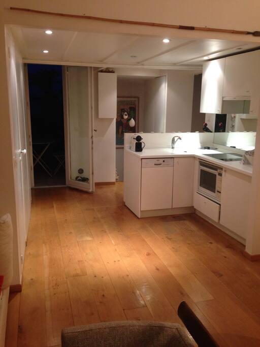 Une cuisine américaine toute équipée (lave-vaisselle et frigo), avec au fond à droite l'escalier pour monter dans la chambre