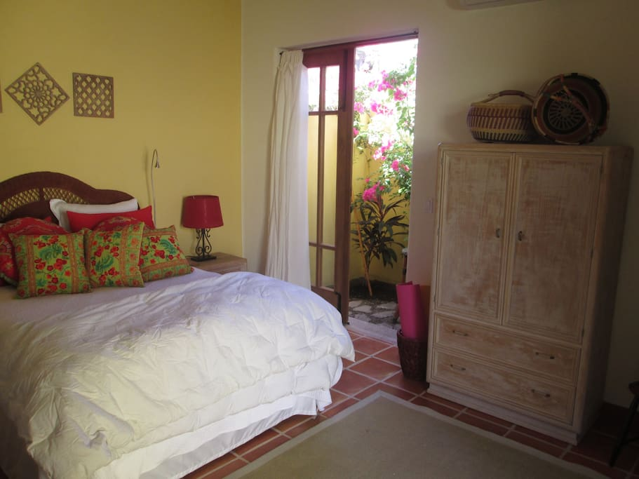 Guest room has a queen bed with a  small garden and adjoining bathroom.
