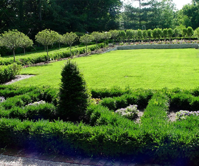 Formal lawn and gardens with boxwood borders.