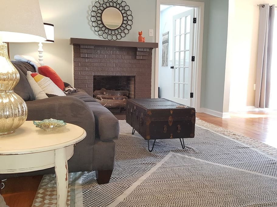 Enjoy the open living room with gas fireplace. The glass door leads to a room with a twin bed.