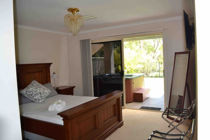 The main bedroom has its own en-suite and TV. Sliding door leading out on to the back verandah over looking the water and access to the spa.