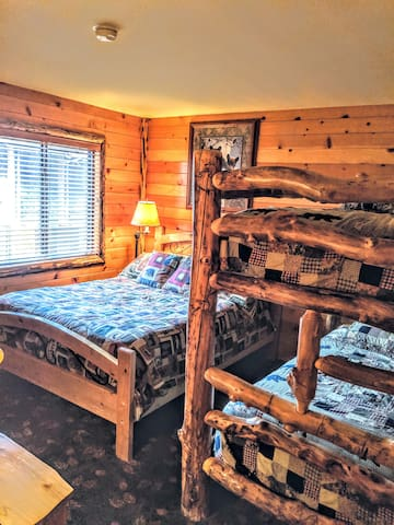 Guest bedroom with queen bed and twin bunk bed.