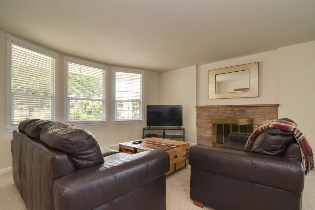 The living room has plenty of seating and a fireplace