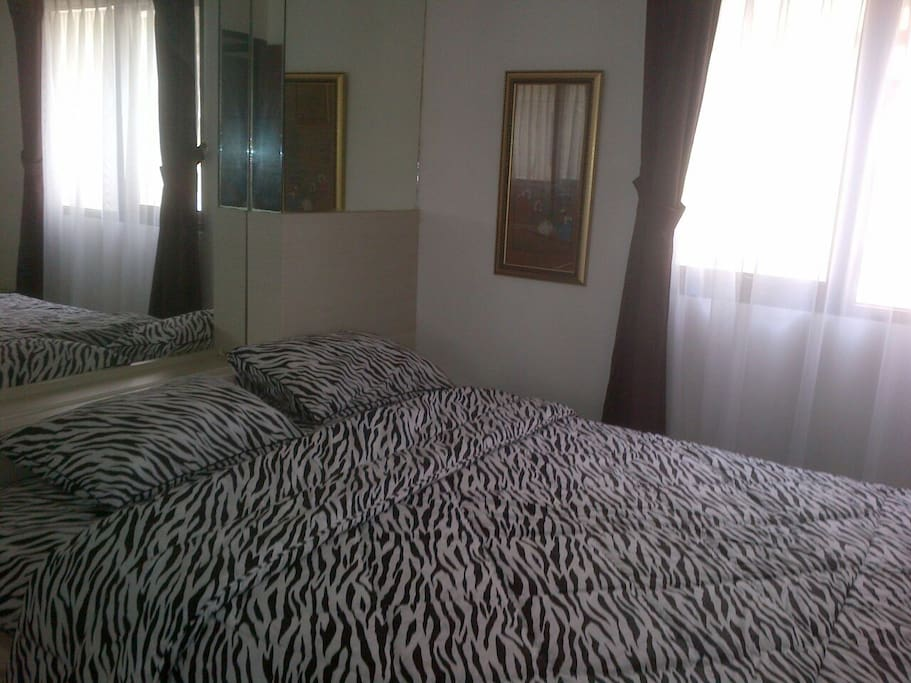 Master bedroom with parquete tile equiped with queen size bed, wardrobe, drawers & air conditioning