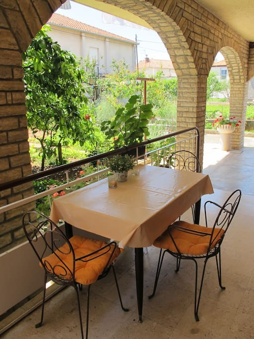 Terrace in front of the apartment, with a view to garden, protected from the sun.