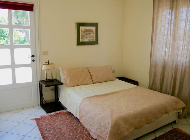 Chambre à coucher avec accès à la terrasse privée.