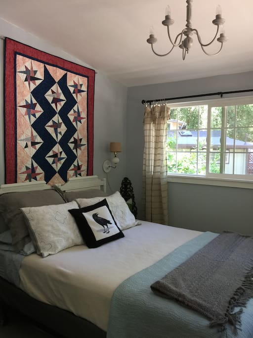 Bedroom with queen bed, extra pillows, and redwood forest views.