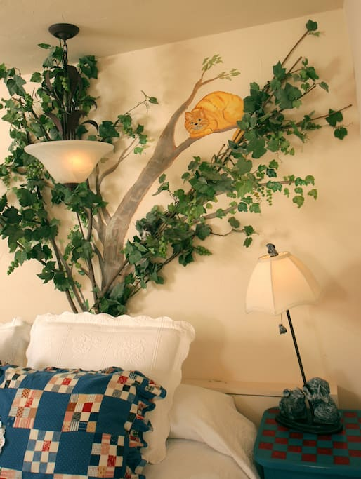 The Cheshire Cat is perched up in the tree that serves a headboard to the king bed.