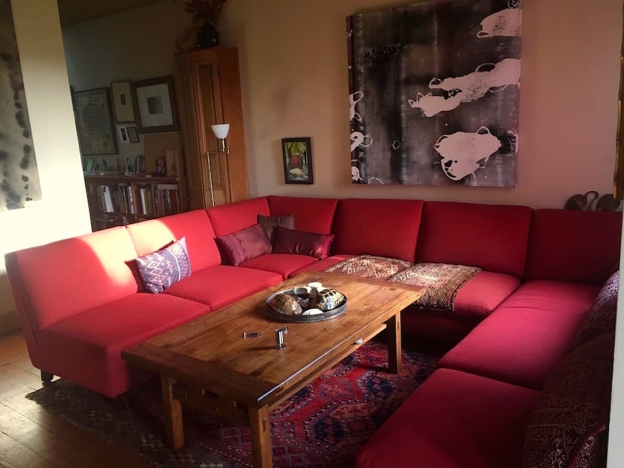 Living room full of art open to kitchen and dining