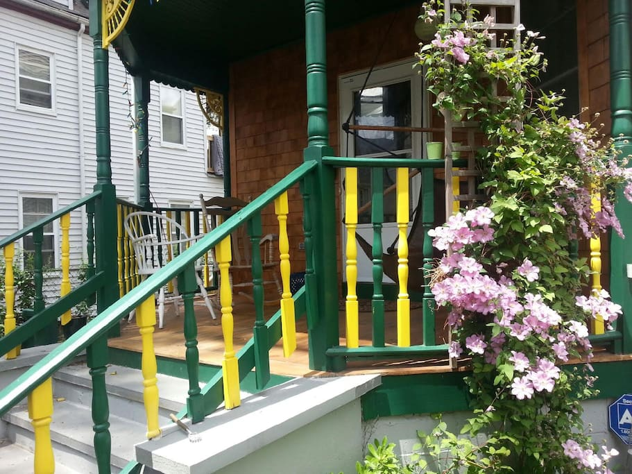 Front porch with climbing flowers, and seating area for hanging out.