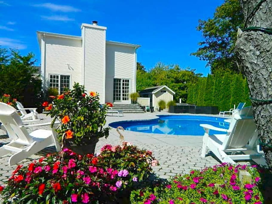 Outdoor pool deck with full dining table, chaise lounges and Adirondack chairs