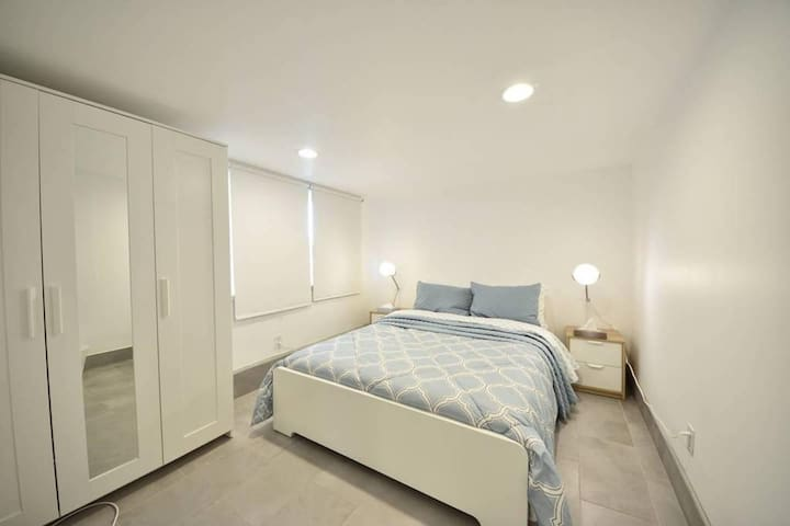 Queen size bed with closet with beach towels and bathrobes