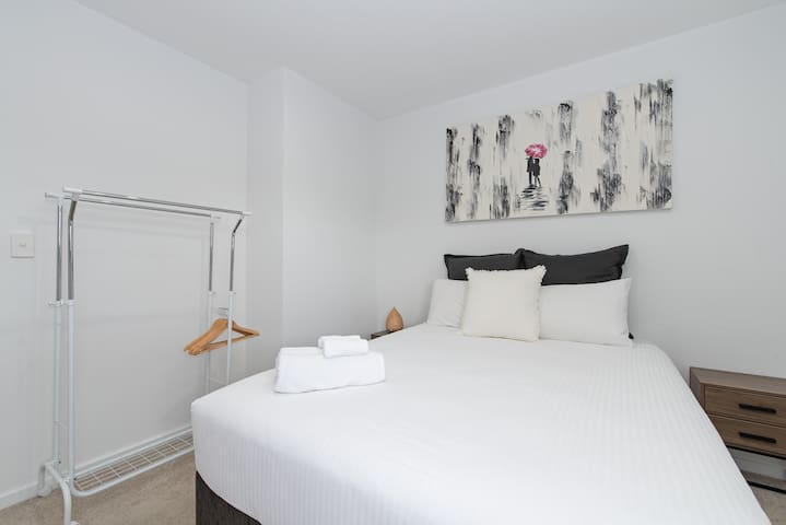 The master bedroom comes with a premium queen-sized bed, bedside tables and clothing rack for your belongings.