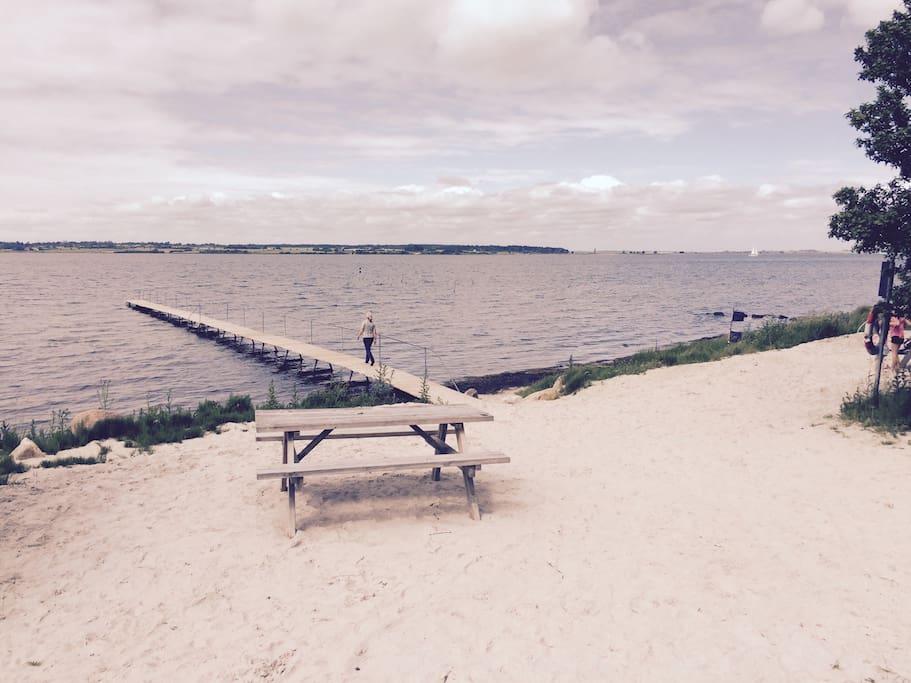 Lille sandstrand med badebro neden for sommerhuset