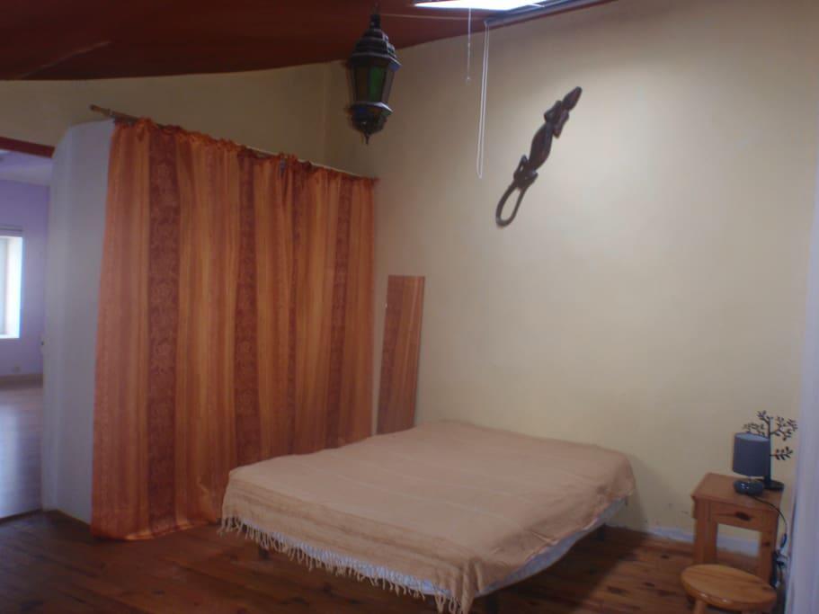 La première chambre avec un lit 2 places, grand placard, table de chevet et velux.