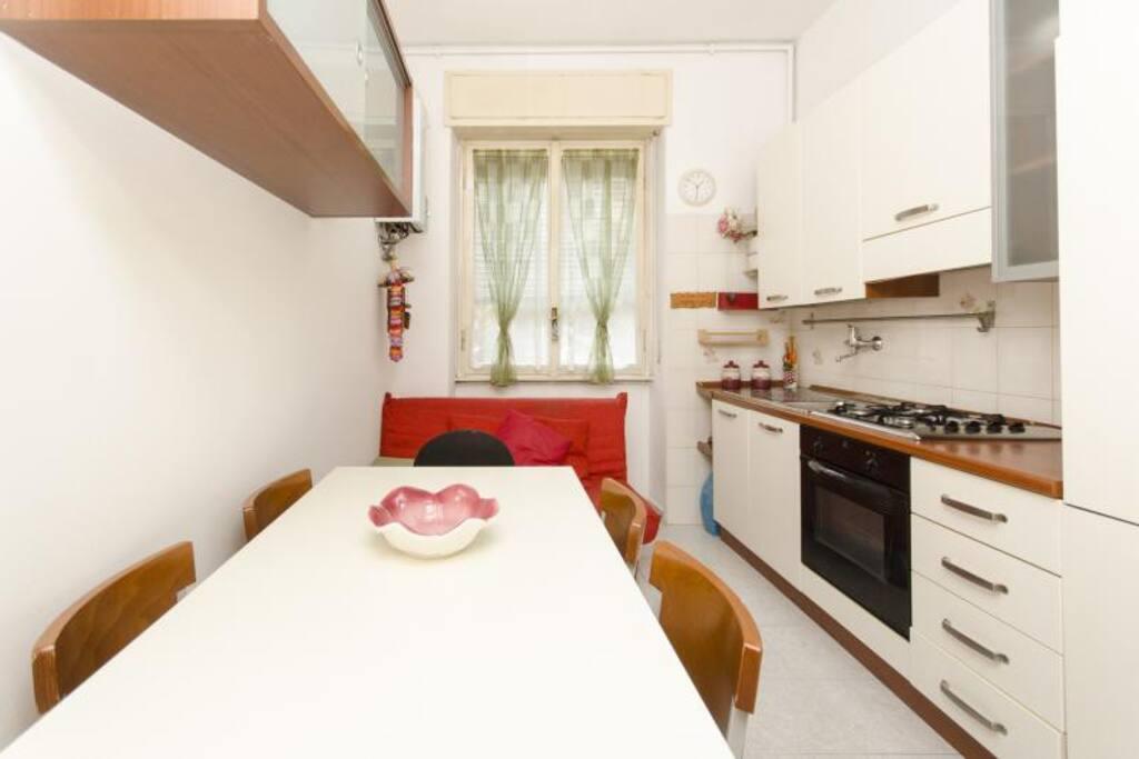 Cucina abitabile con tavolo e divano letto