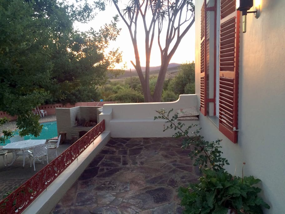 Sunset view with swimming pool and an outside sitting area with braai facility.