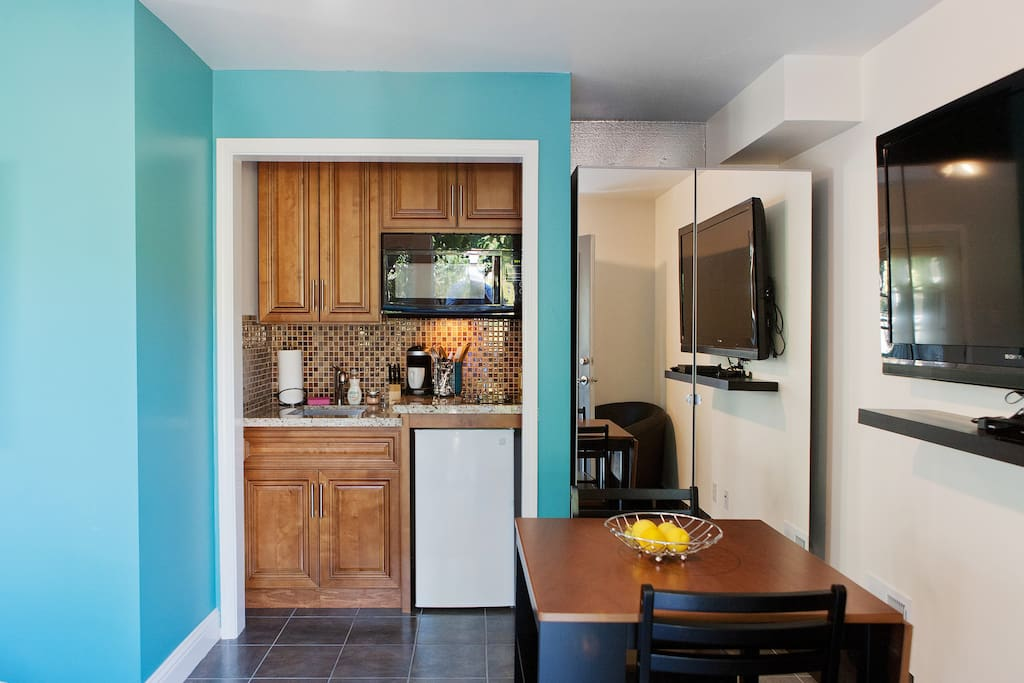 Small kitchenette with cooktop, mini fridge, and a small dining table.