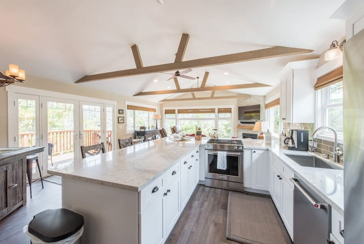 The gourmet kitchen features quartz countertops,  stainless steel appliances, and a large breakfast bar.