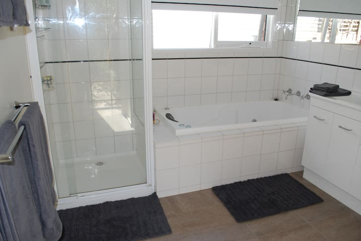 Large bathroom, with shower, spa bath and toilet
