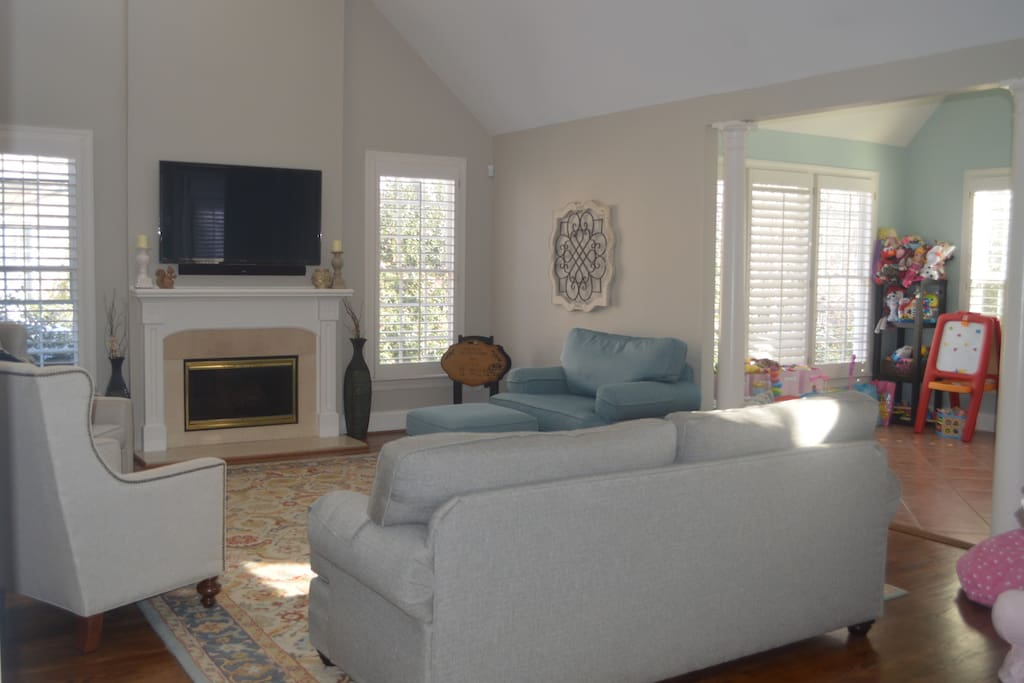 Large living room, open to kitchen, and sunroom. Couch is also a high end pull out bed.