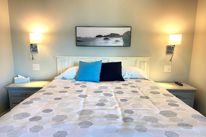 Comfortable Queen bed with end tables that have reading lamps and USB ports for your devices.