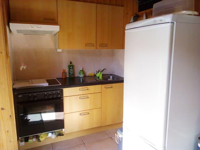 Küche mit Herd Umluftbackofen  Kühlgefrierschrank und Mikrowelle