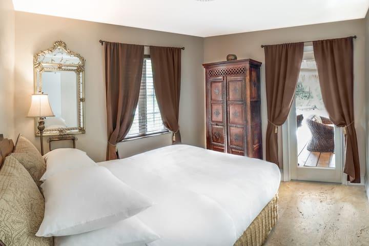 Queen bedroom with door to outdoor living room.