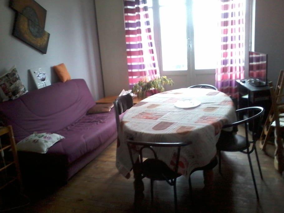 Salon aux couleurs pastels et fraîches, exposé plein sud avec canapé lit.