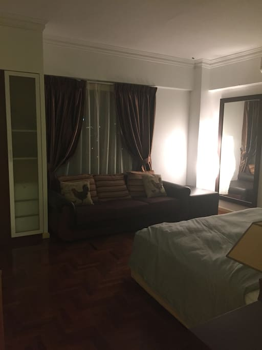 Bedroom furnished with 3 seater sofa and wardrobe