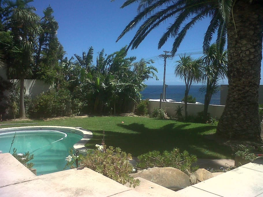 gorgeous sheltered lawned garden and pool area, with great sea view