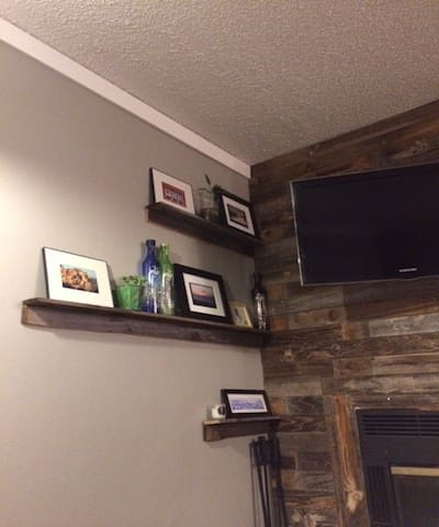 Reclaimed wood wall with flatscreen TV and working fireplace.