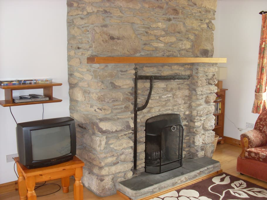 Warm, inviting sitting room with large real fireplace, perfect for cosy nights in!