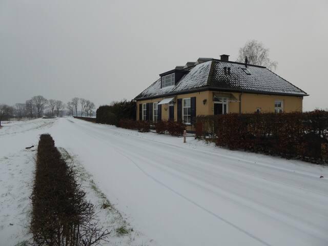 De dijk en ons huis in de winter